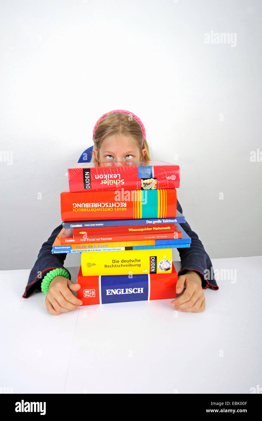 squinting school girl with a stack of school books - Stock Image
