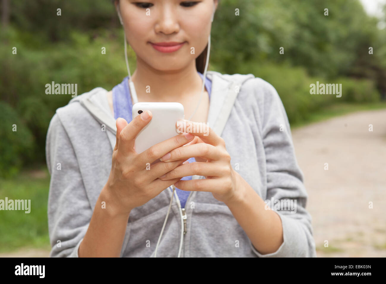 Close up of young female runner selecting music from smartphone in park - Stock Image