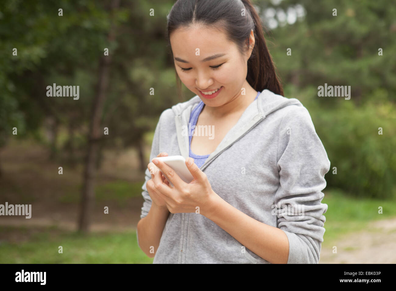 Young female runner selecting music from smartphone in park - Stock Image