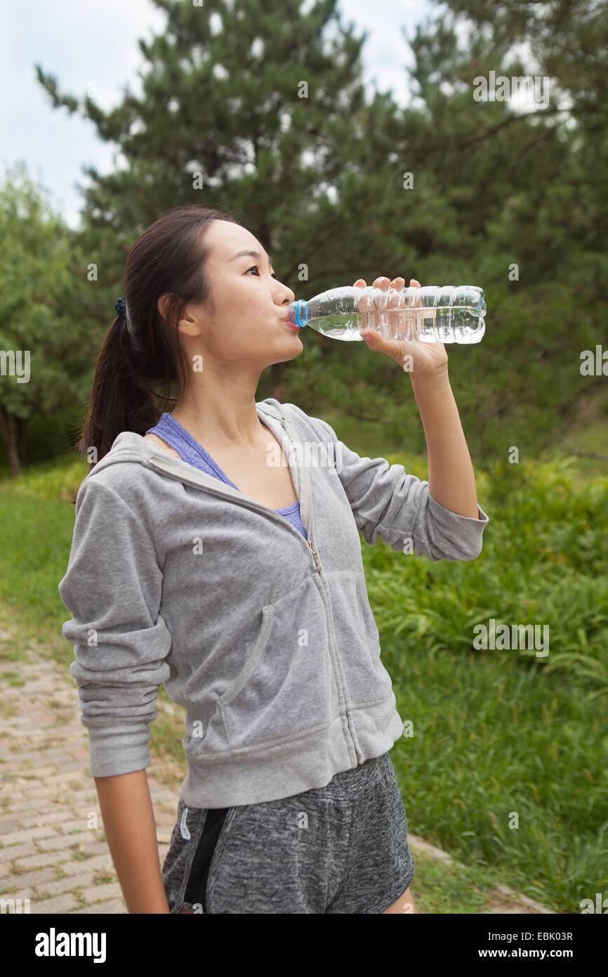 Young female runner drinking bottled water in park - Stock Image