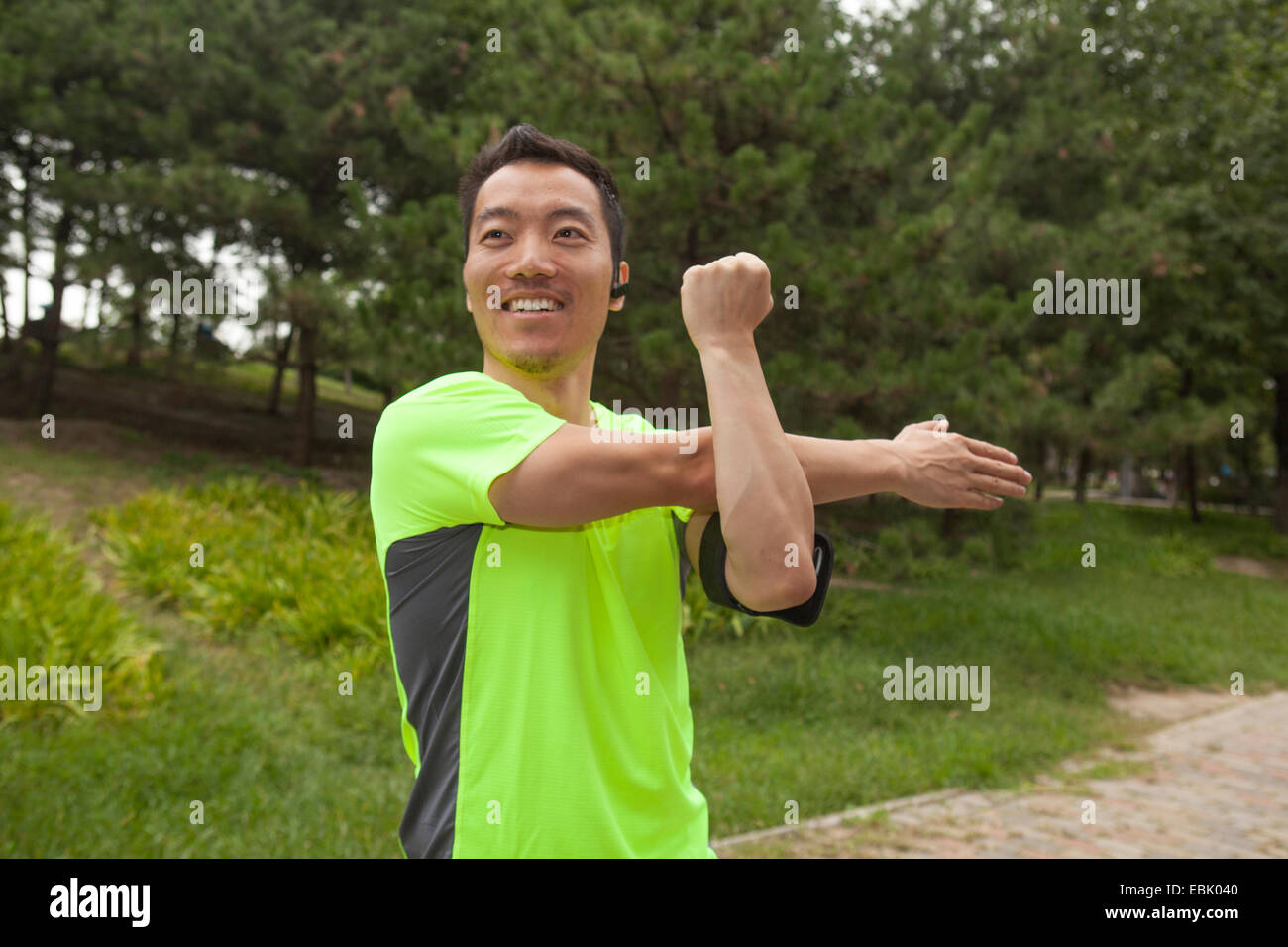Young male runner stretching arms in park - Stock Image