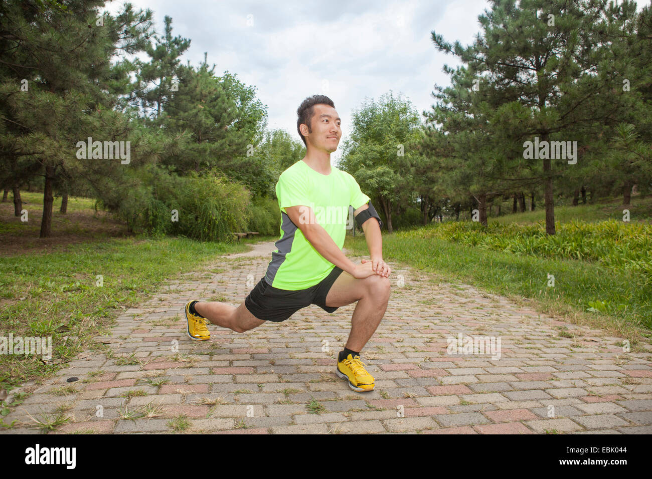 Young male runner stretching legs in park - Stock Image