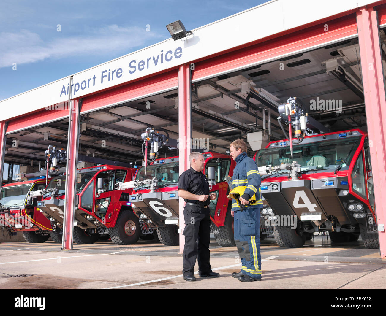 Officer and fireman in front of fire engines in airport fire station - Stock Image