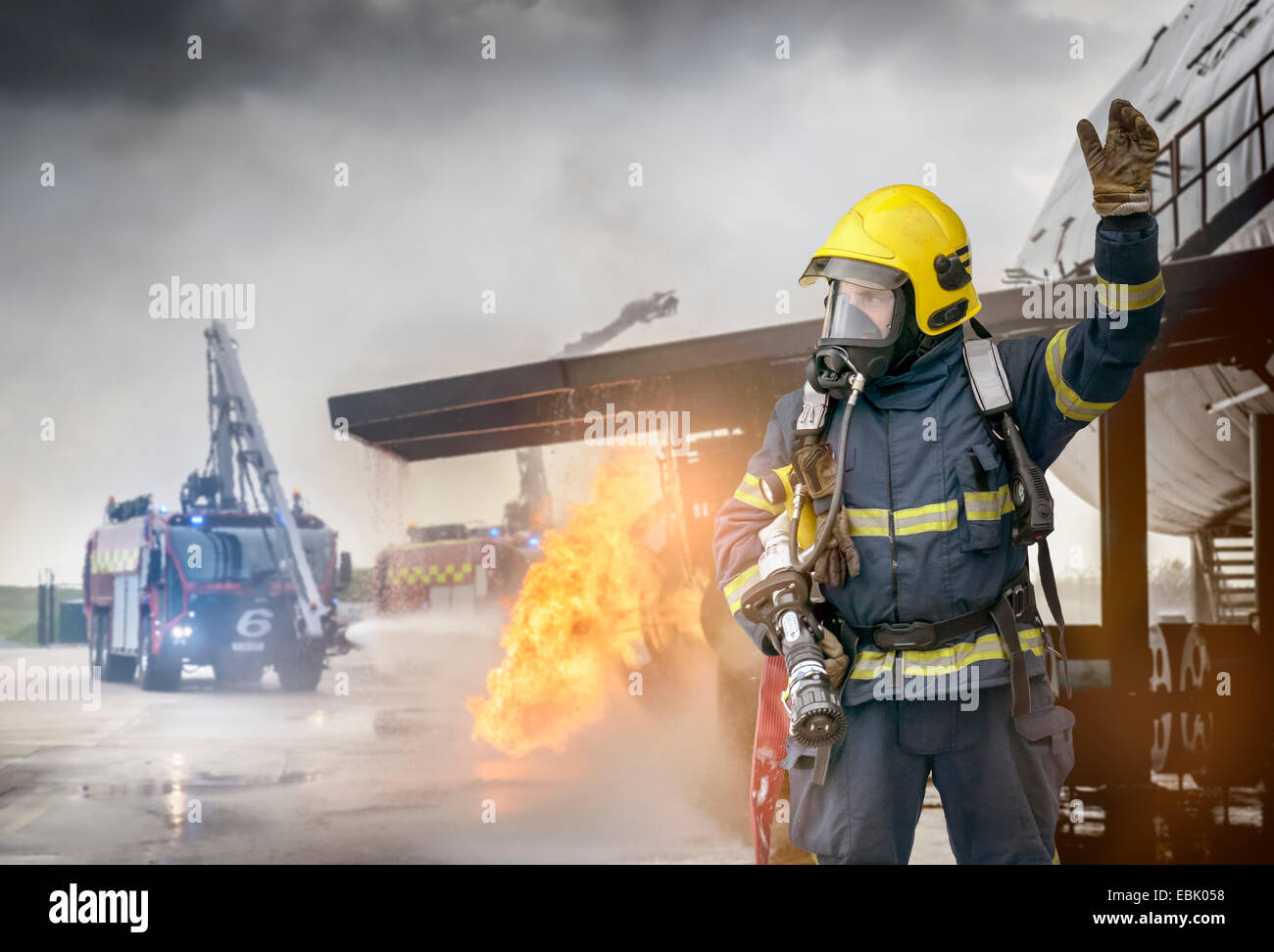 Portrait of fireman in front of simulated fire at airport training facility - Stock Image