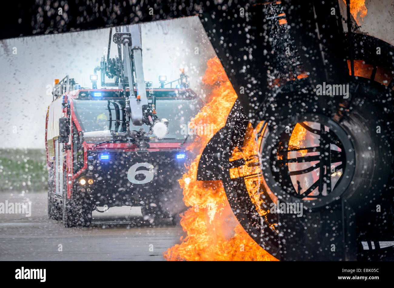 Fire engine spraying water on simulated fire at airport training facility - Stock Image