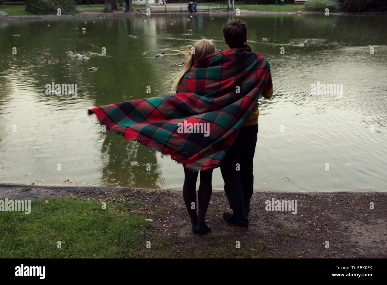 Rear view of young couple wrapped in blanket on park lakeside - Stock Image