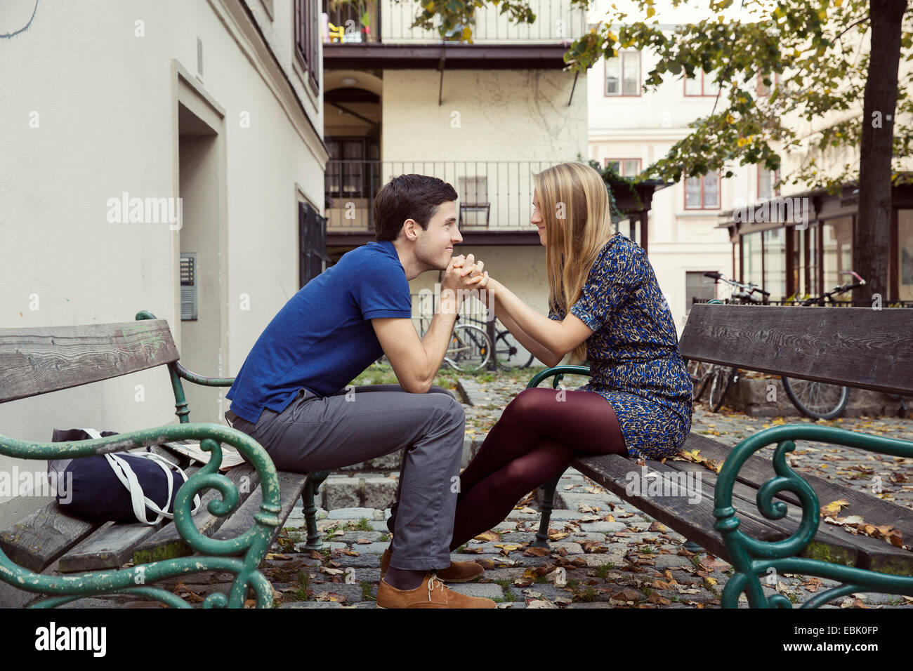 Young couple holding hands from opposite park benches - Stock Image