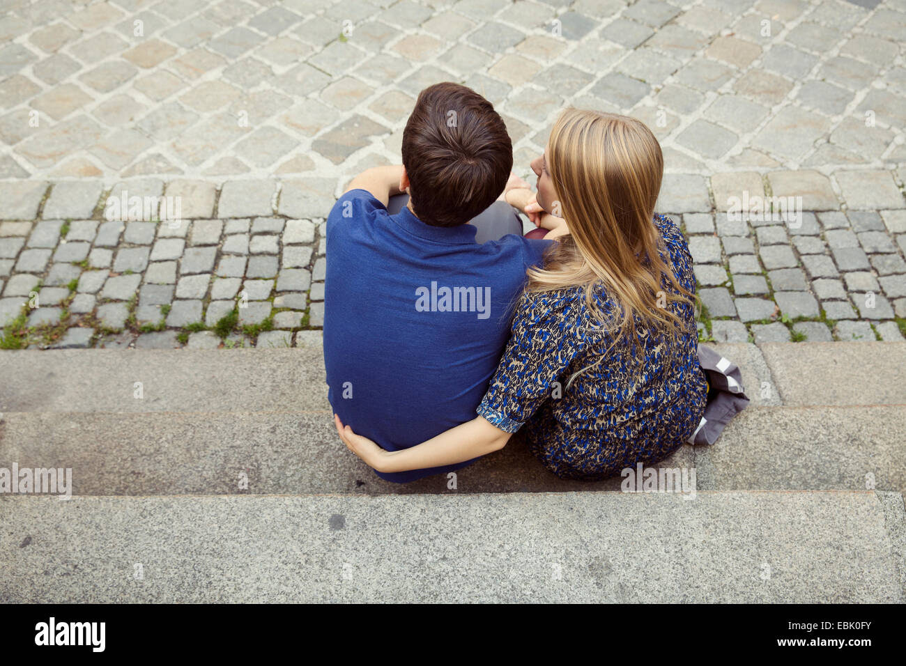 Rear view of young couple sitting on street sidewalk - Stock Image