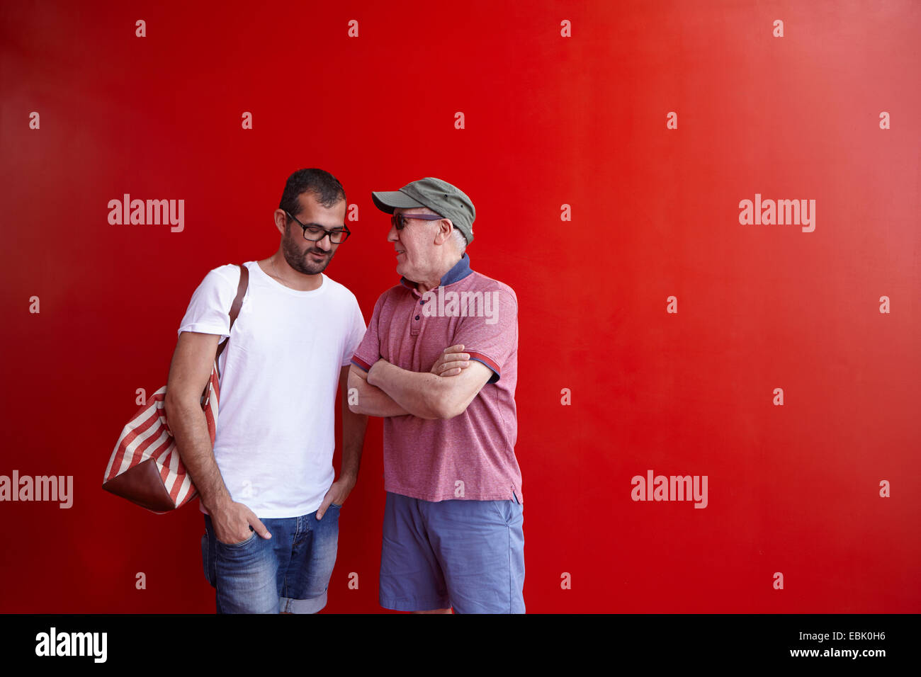 Mid adult man and senior man talking, standing against red background Stock Photo