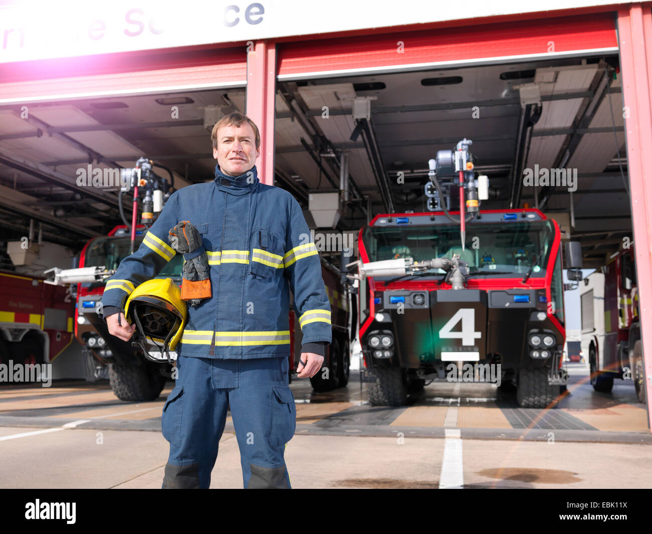 Portrait of fireman in front of fire engines in airport fire station - Stock Image