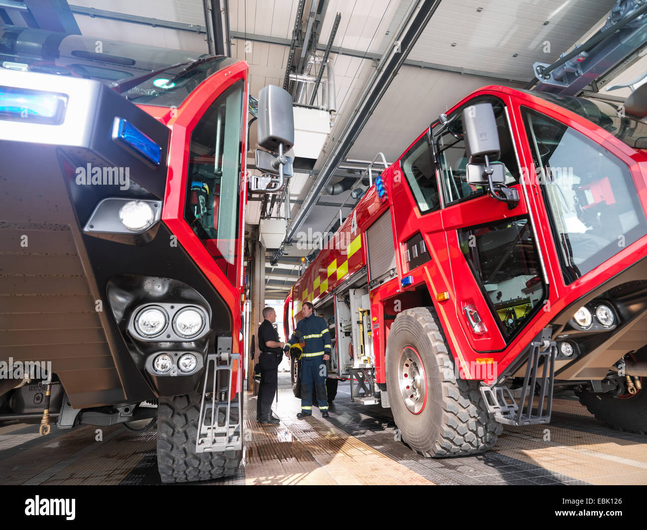 Firemen in discussion between fire engines in airport fire station - Stock Image