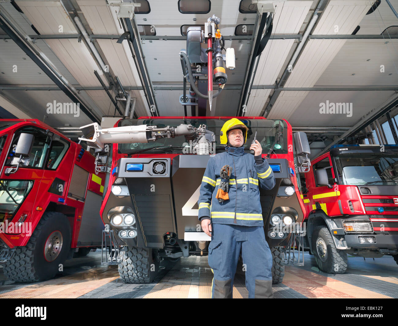 Fireman using walkie talkie in front of fire engines in airport fire station - Stock Image