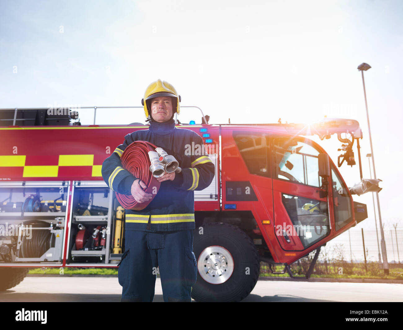 Portrait of fireman in front of fire engine in airport fire station - Stock Image