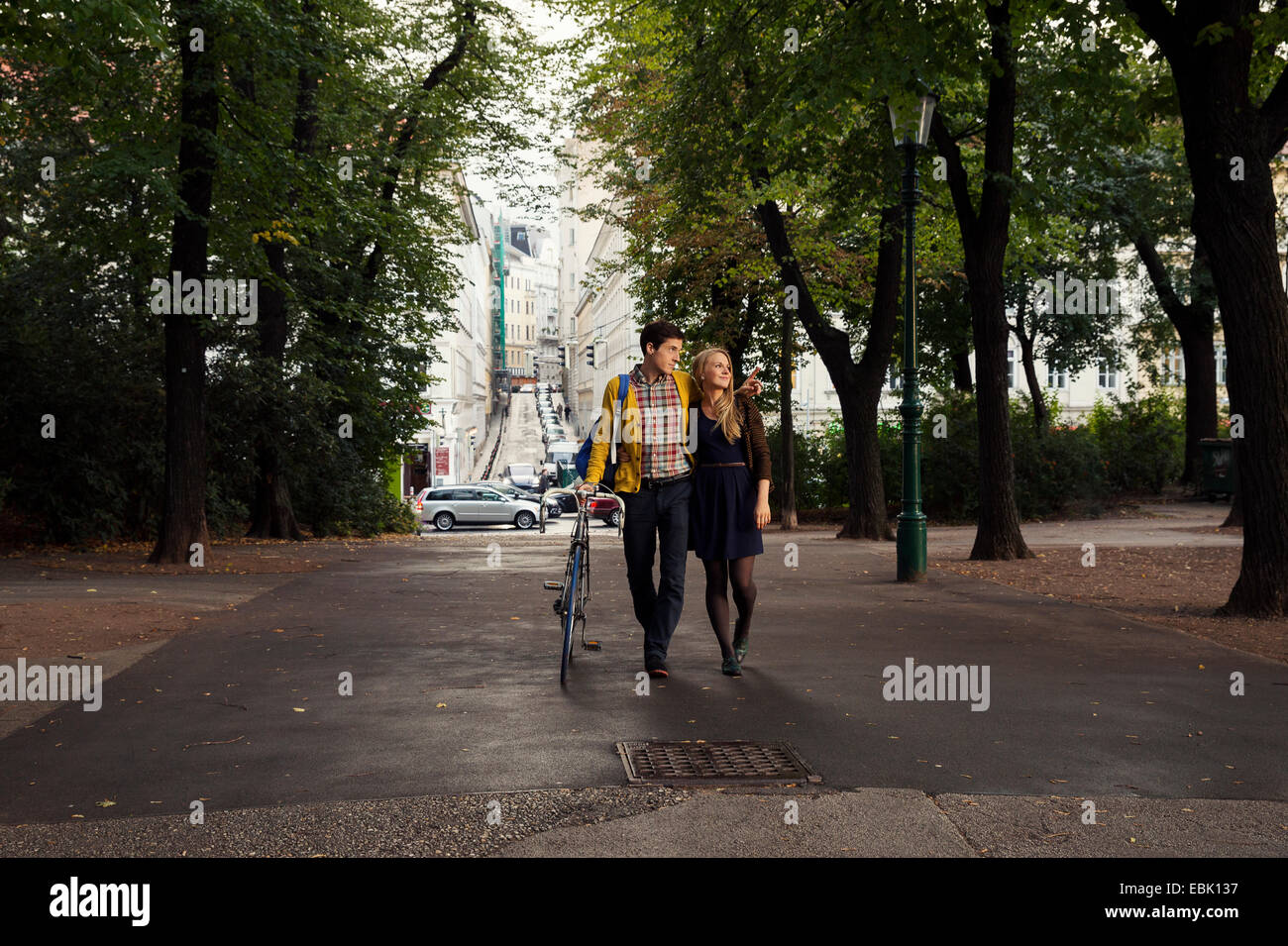 Young couple strolling in tree lined park - Stock Image