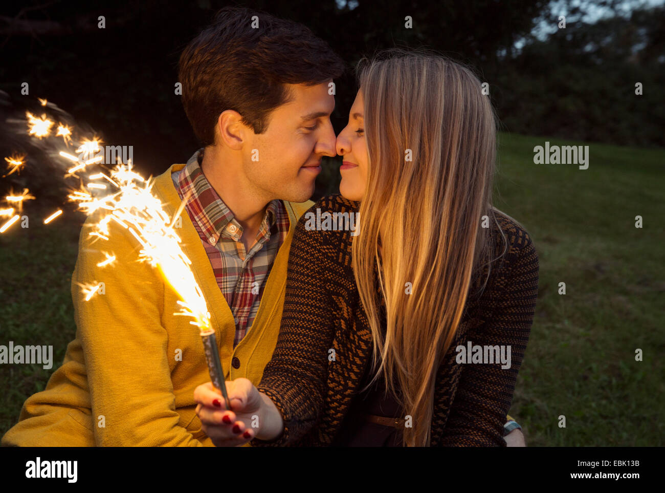 Young couple nose to nose in park holding sparkling firework - Stock Image