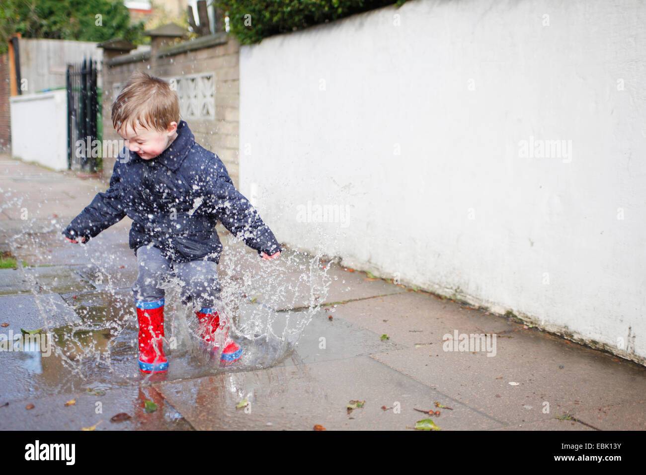 Male toddler in red rubber boots splashing in sidewalk puddle Stock Photo