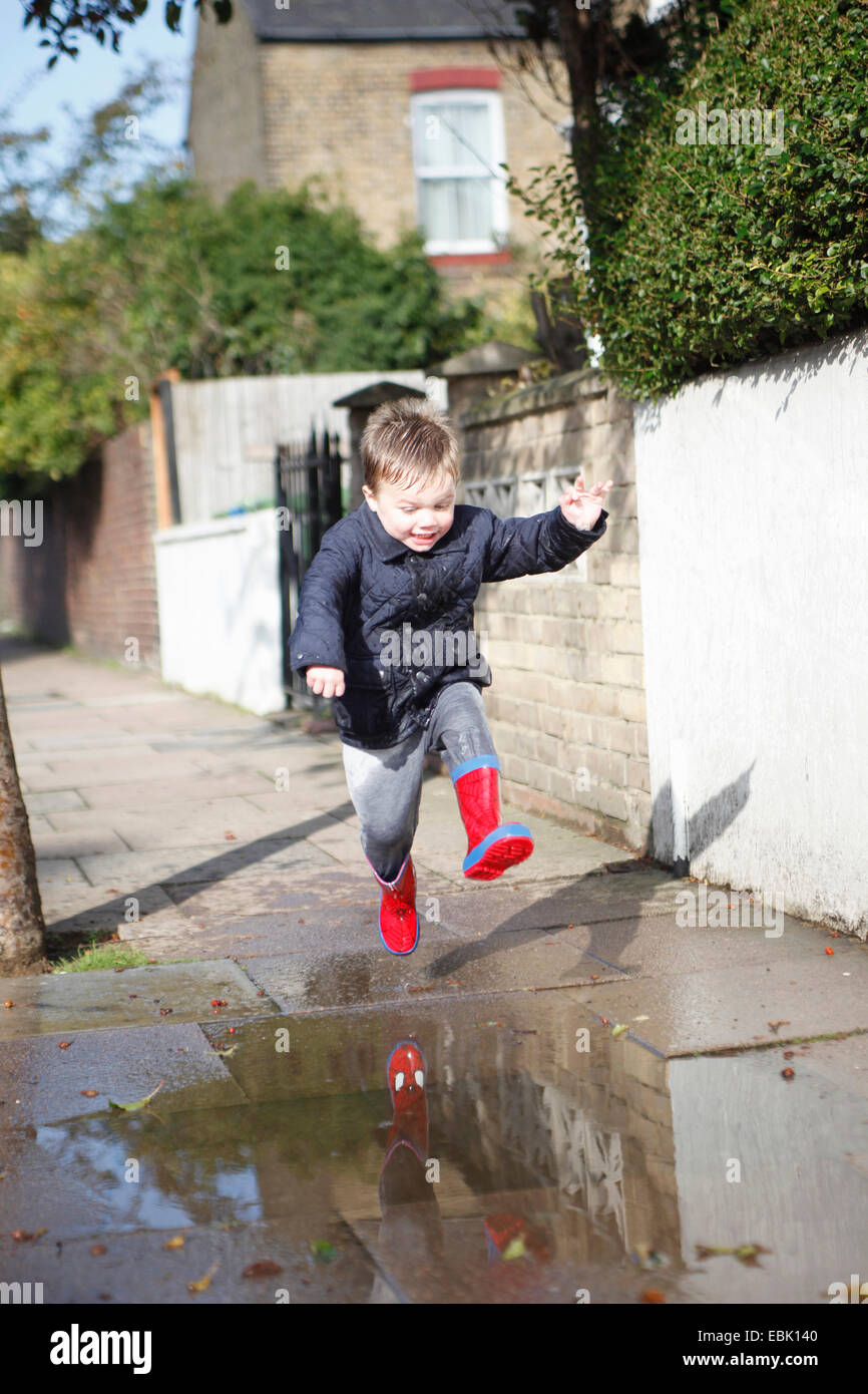 Male toddler in red rubber boots jumping into sidewalk puddle - Stock Image