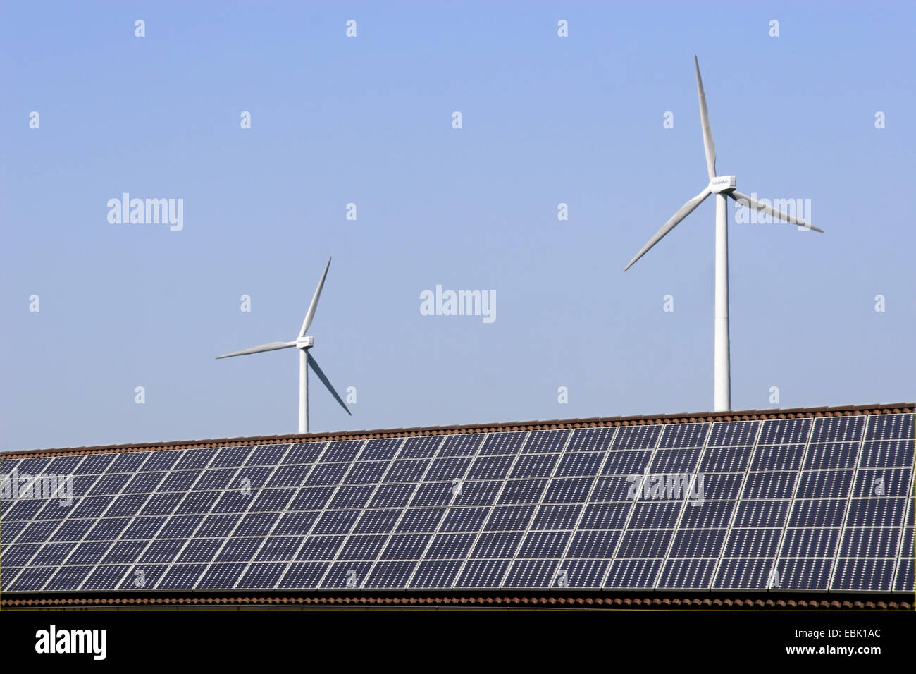 wind power stations looming behind a roof with solar cells, Germany - Stock Image