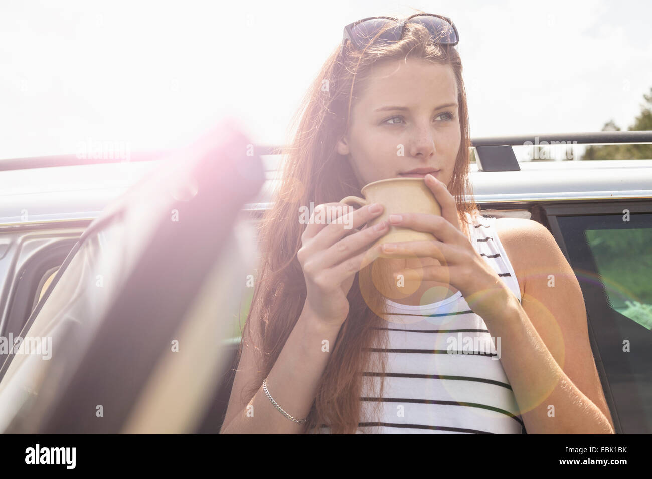 Young woman having coffee break on road trip - Stock Image