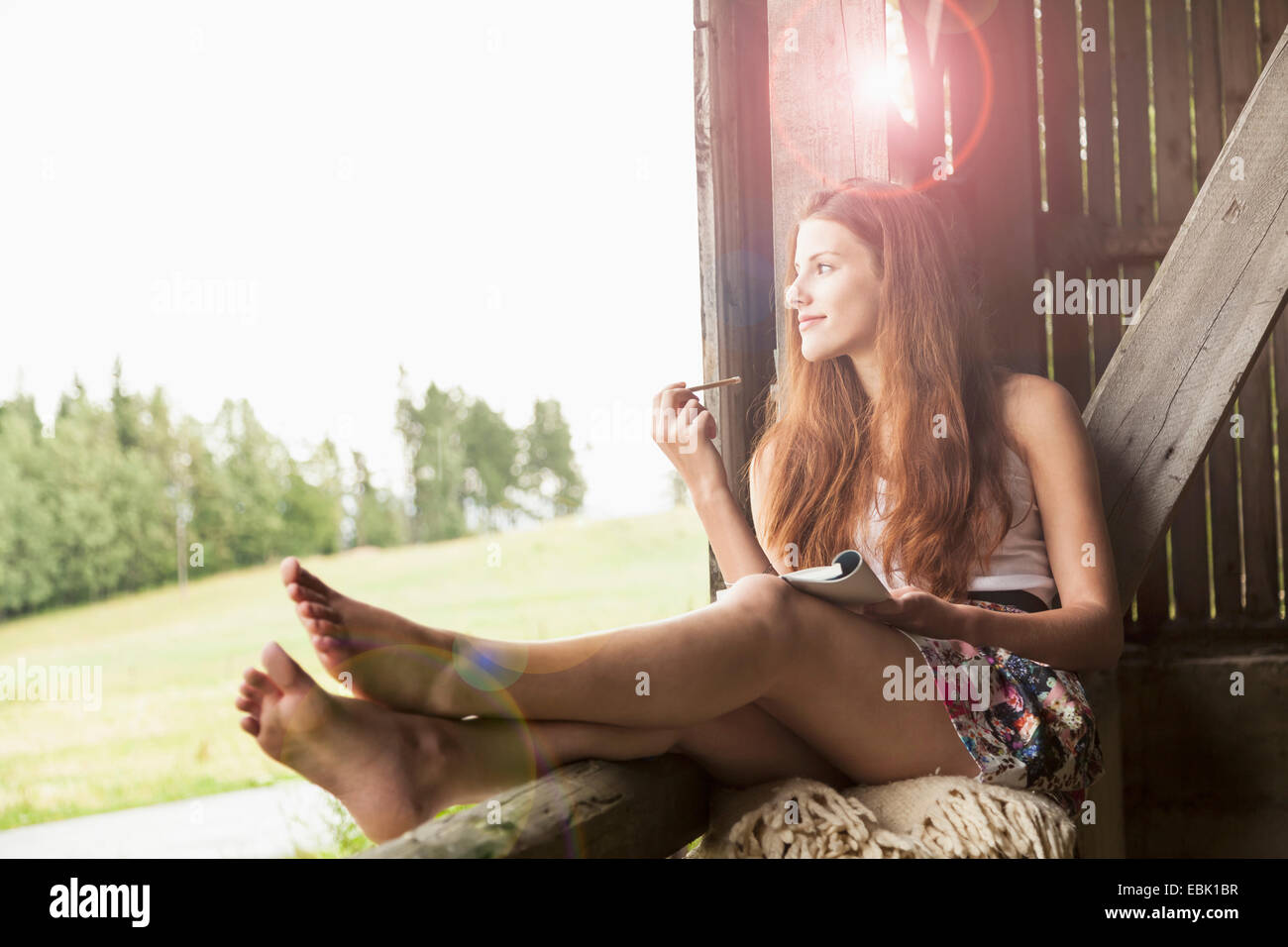 Young woman sitting in barn with notebook - Stock Image