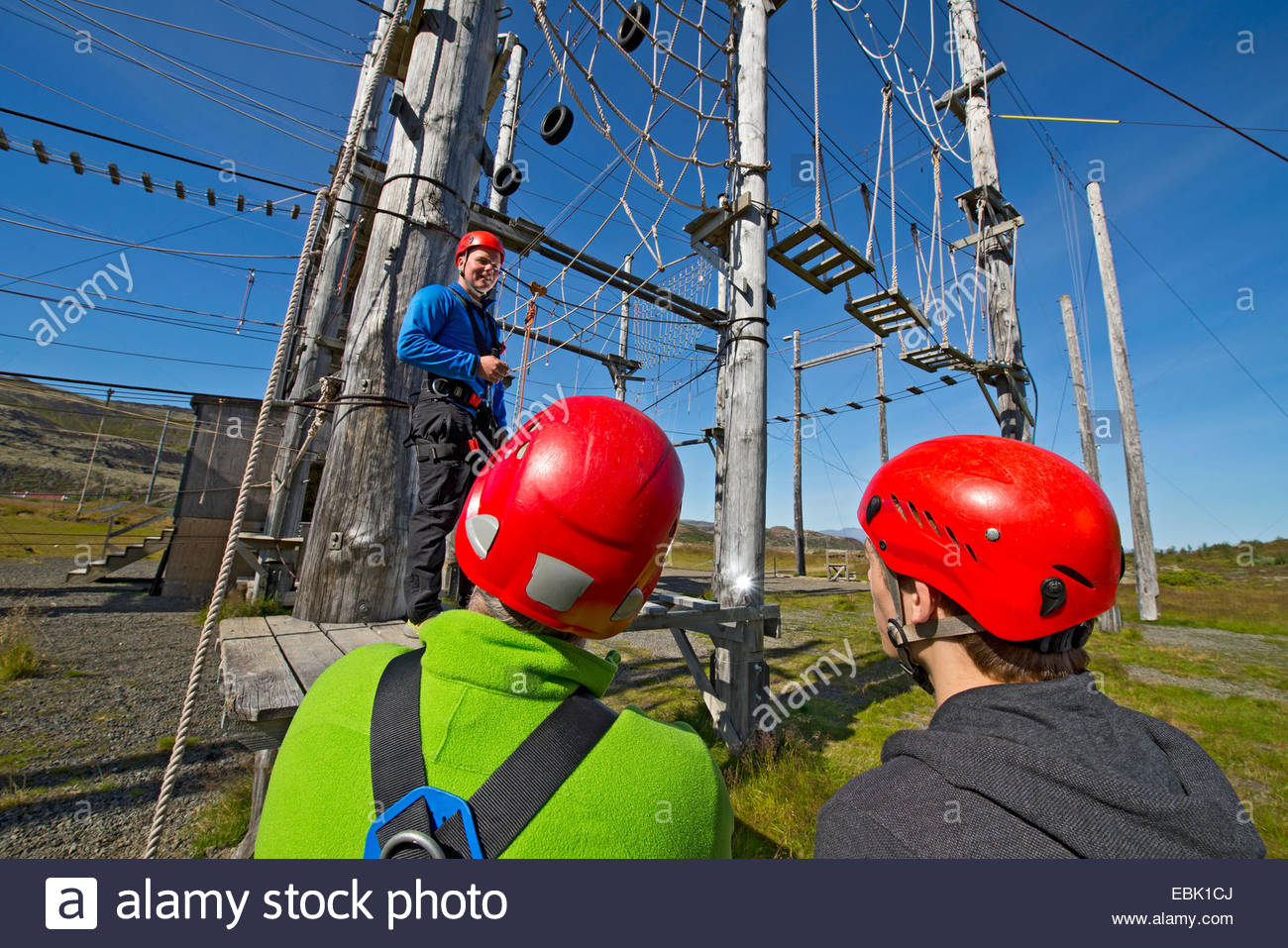 Three people wearing climbing helmets on high rope course - Stock Image