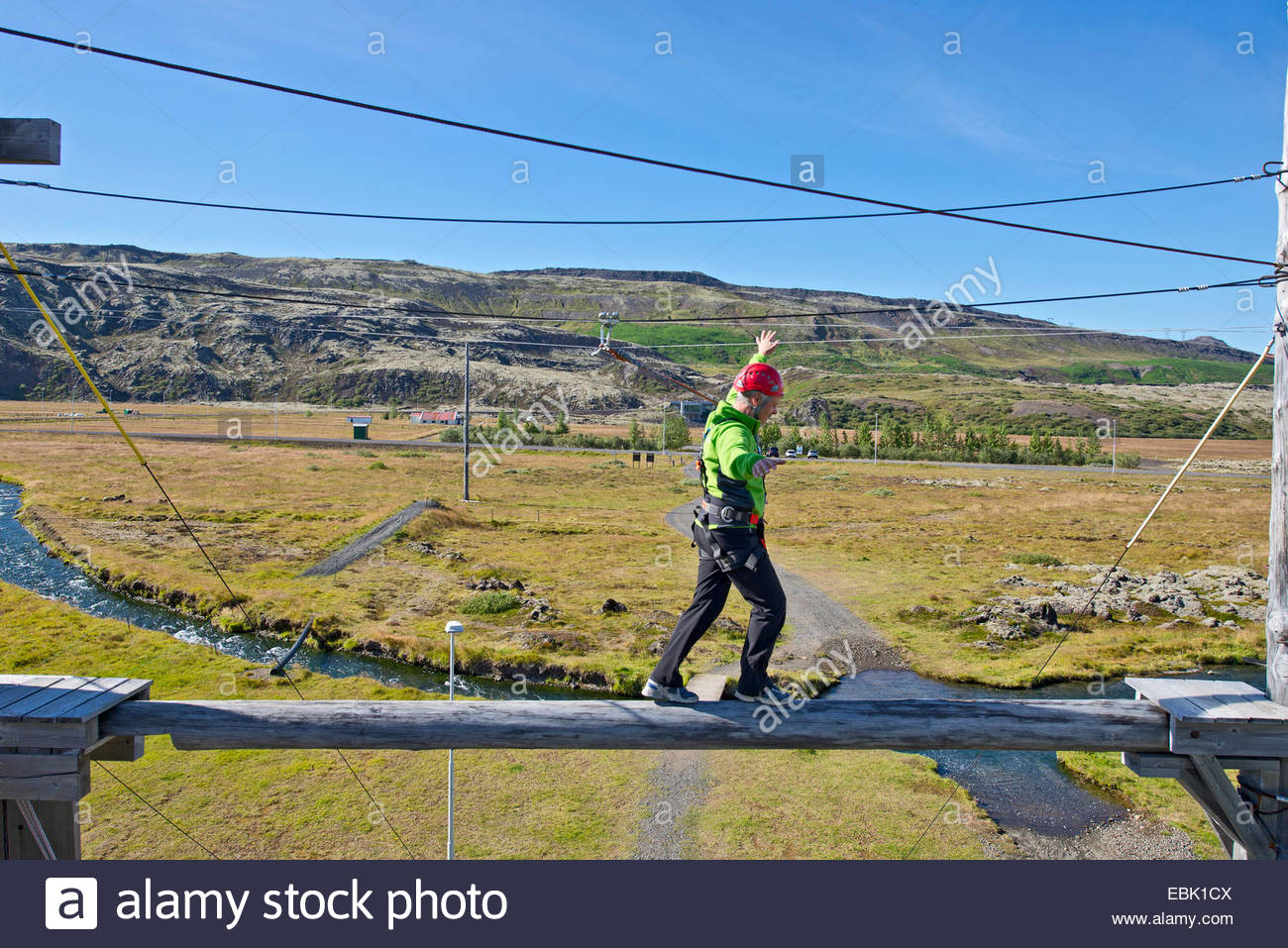 Mature man balancing on wooden plank on high rope course - Stock Image