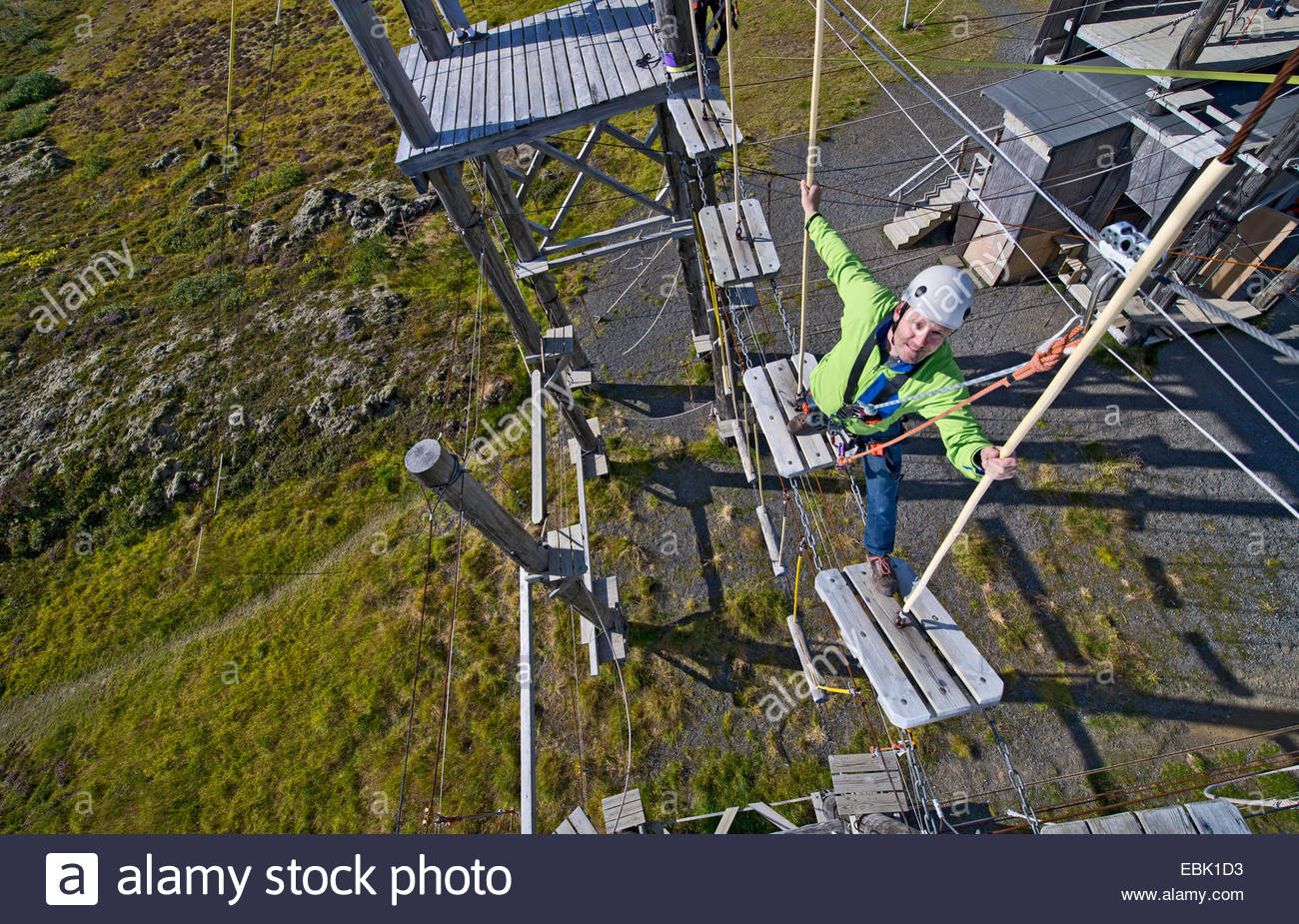 Mature man walking on wooden planks on high rope course Stock Photo