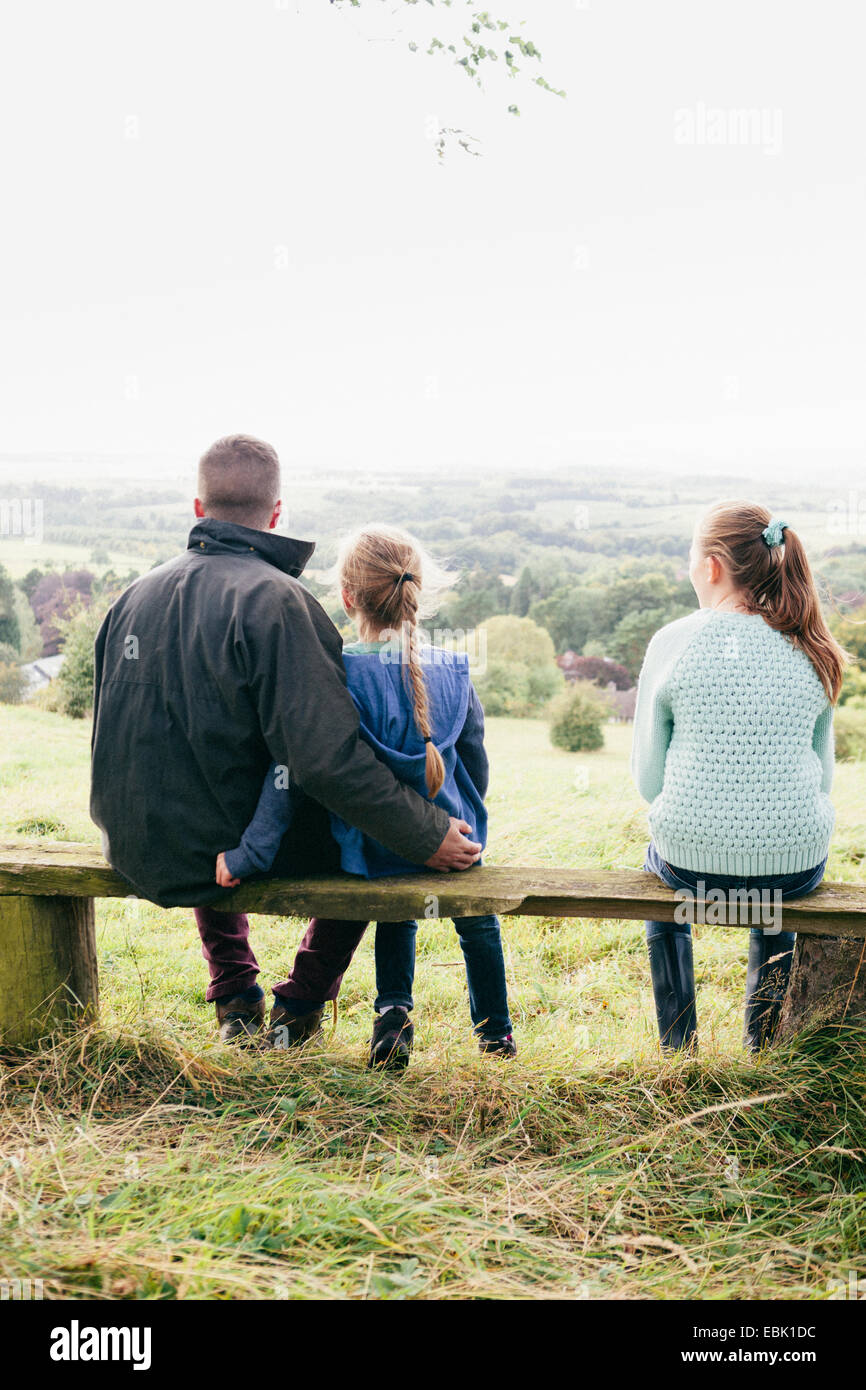 Father sitting with daughters looking at view - Stock Image