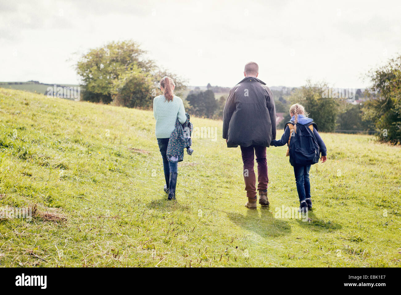 Father and daughters walking in field - Stock Image
