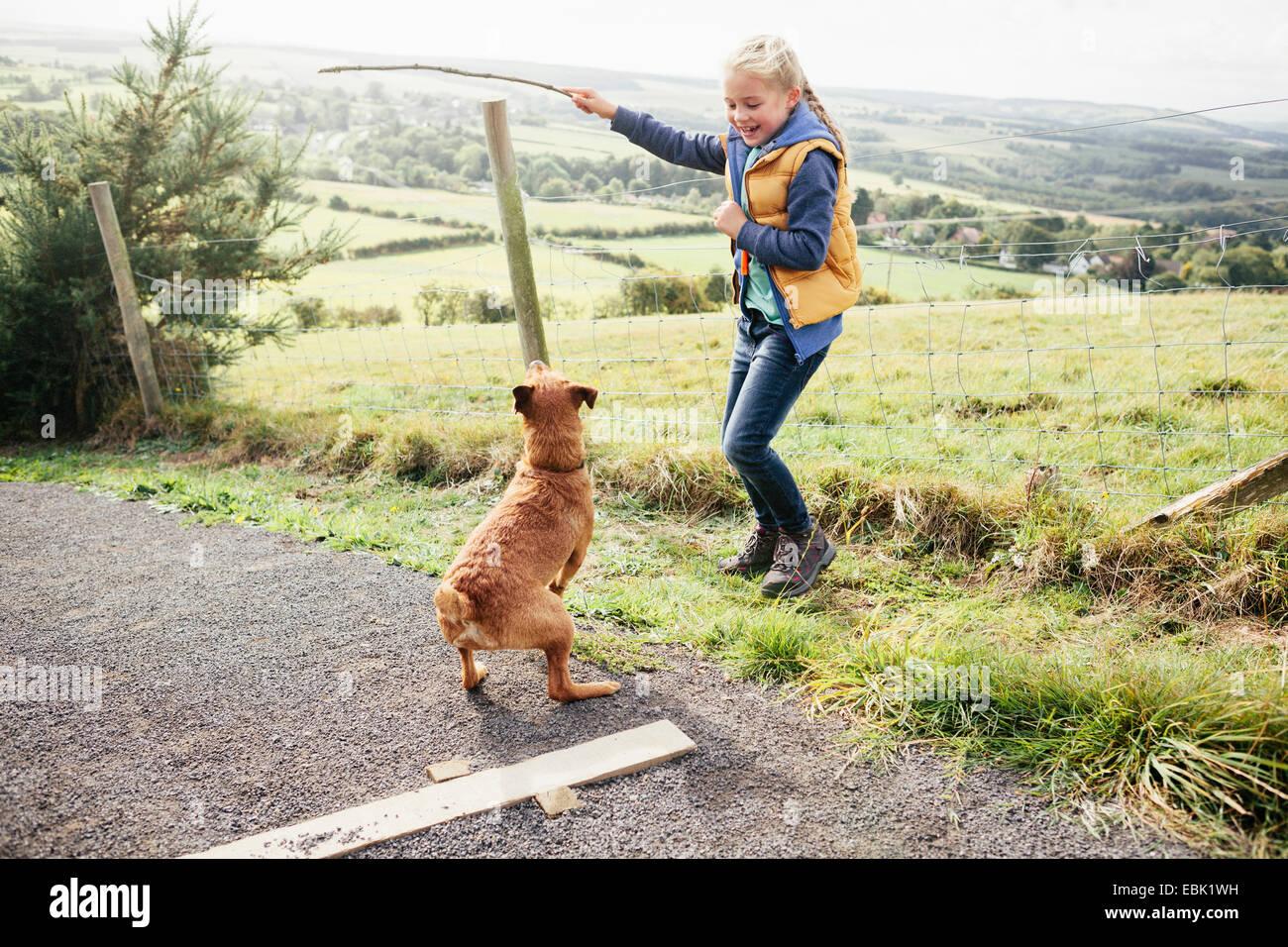 Girl holding stick for pet dog - Stock Image