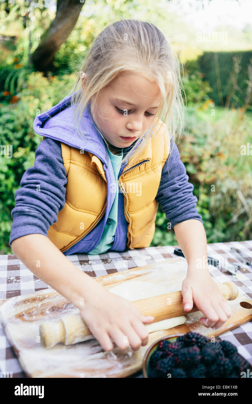Girl rolling pastry - Stock Image