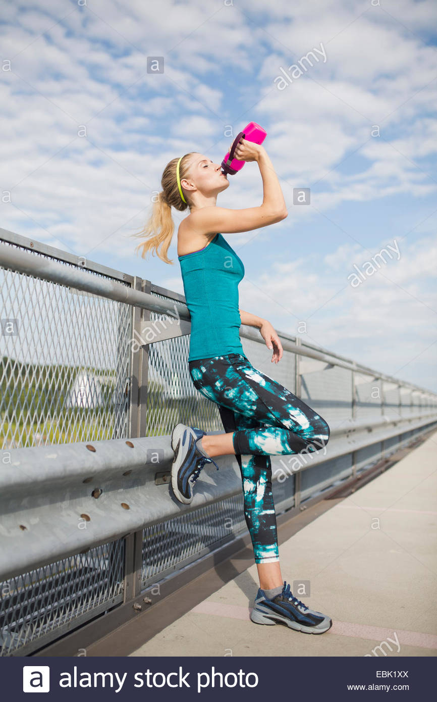 Young woman drinking water from bottle - Stock Image