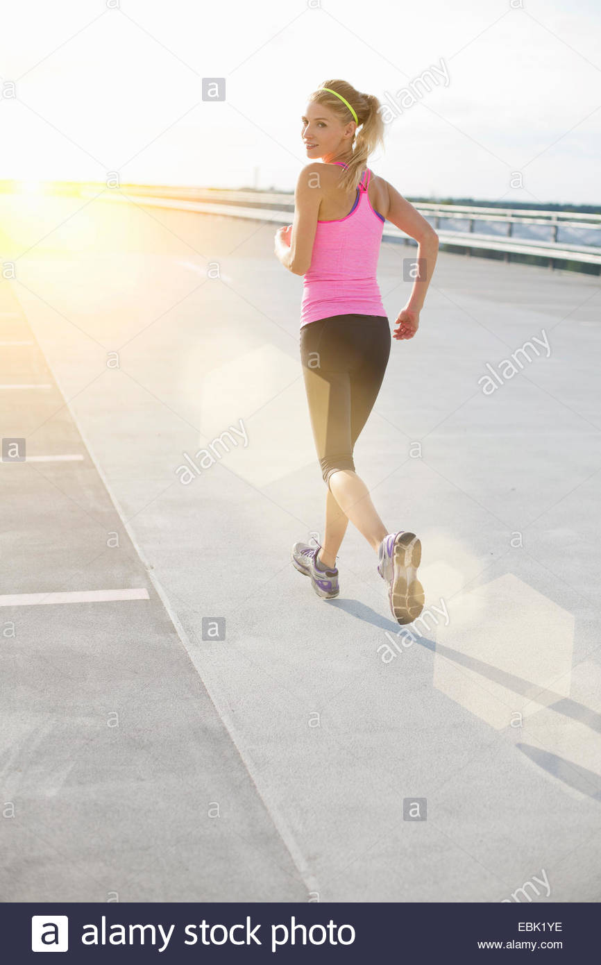 Young woman jogging, looking over shoulder - Stock Image