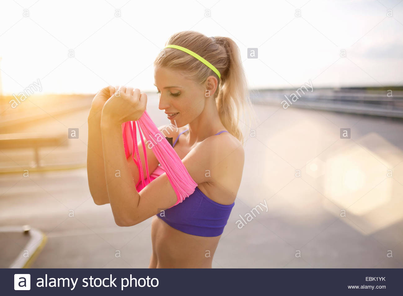 Young woman putting on vest - Stock Image