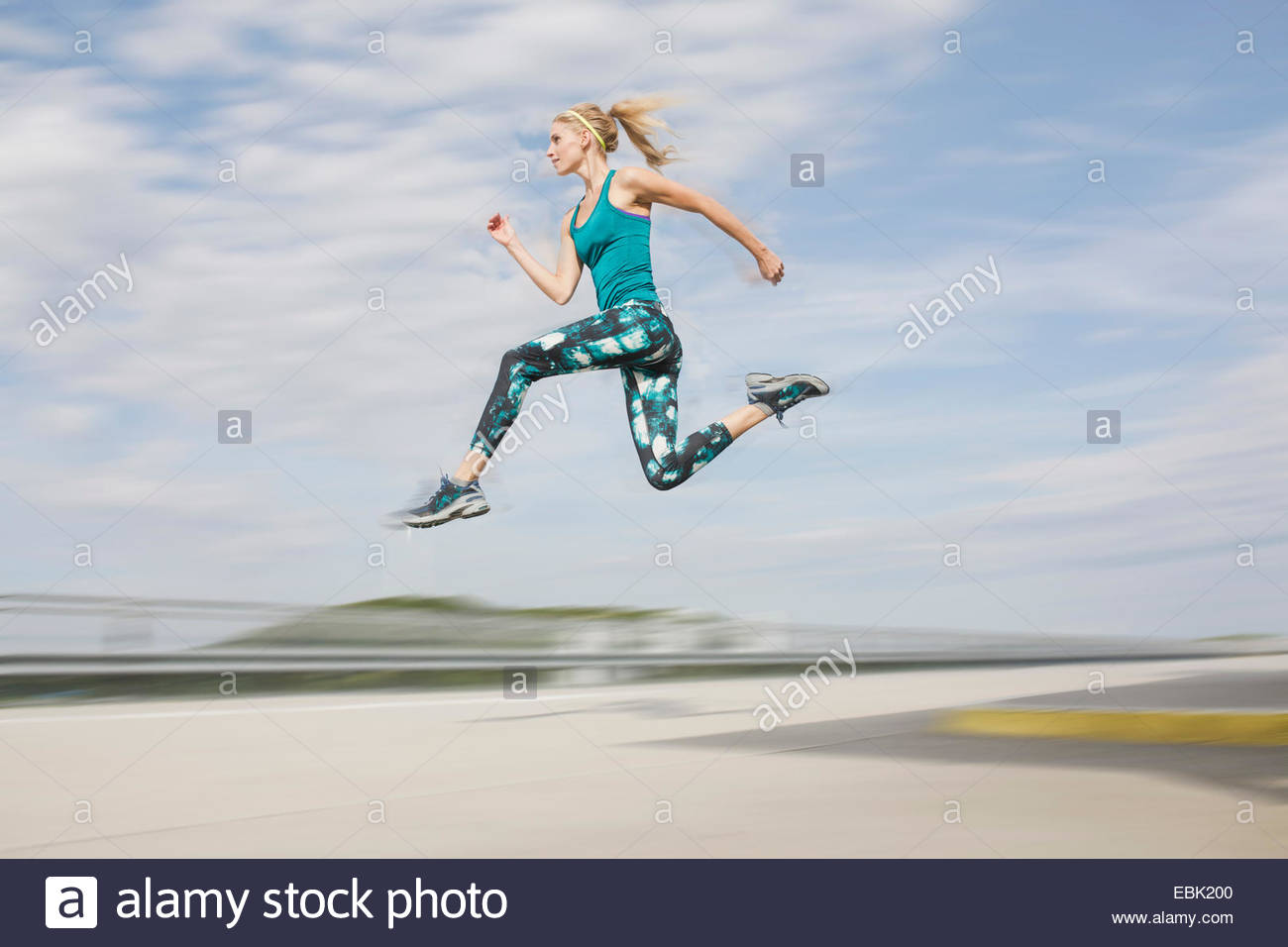 Young woman jumping mid air - Stock Image
