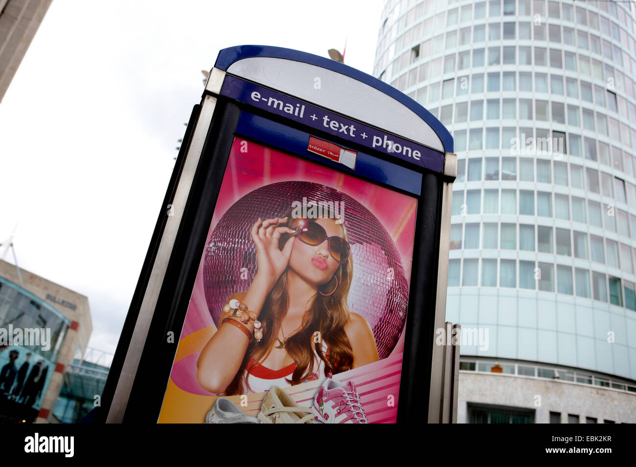 Advertising image on the side of a phone box in central Birmingham with the Rotunda in the background. - Stock Image