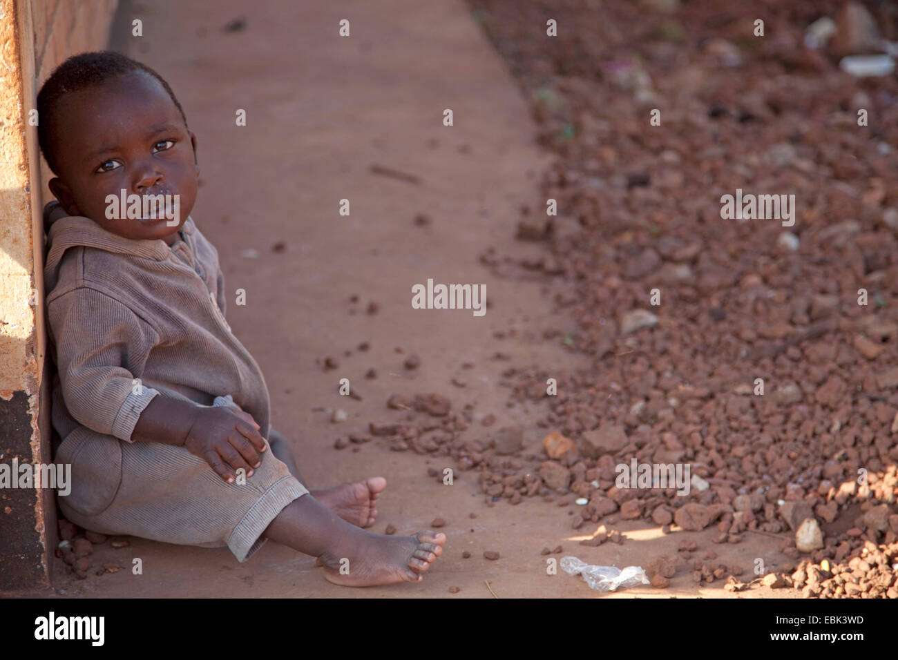 orphan child sitting on concrete ground at the local orphanage, Burundi, Near National Parc de la Ruvubu, Cankuzo - Stock Image
