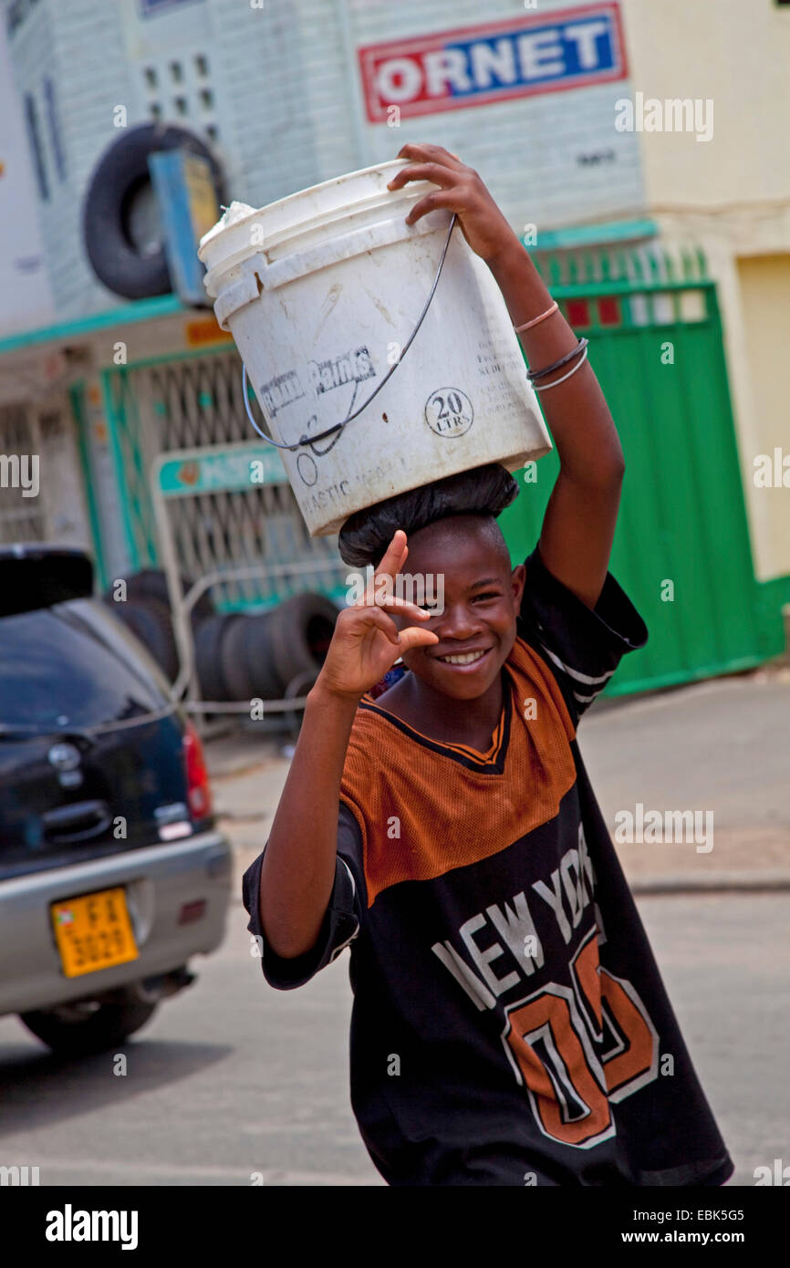 boy capping beaks while carrying a water bucket on his head through heavy traffic, Burundi, Bujumbura Mairie, Bujumbura - Stock Image