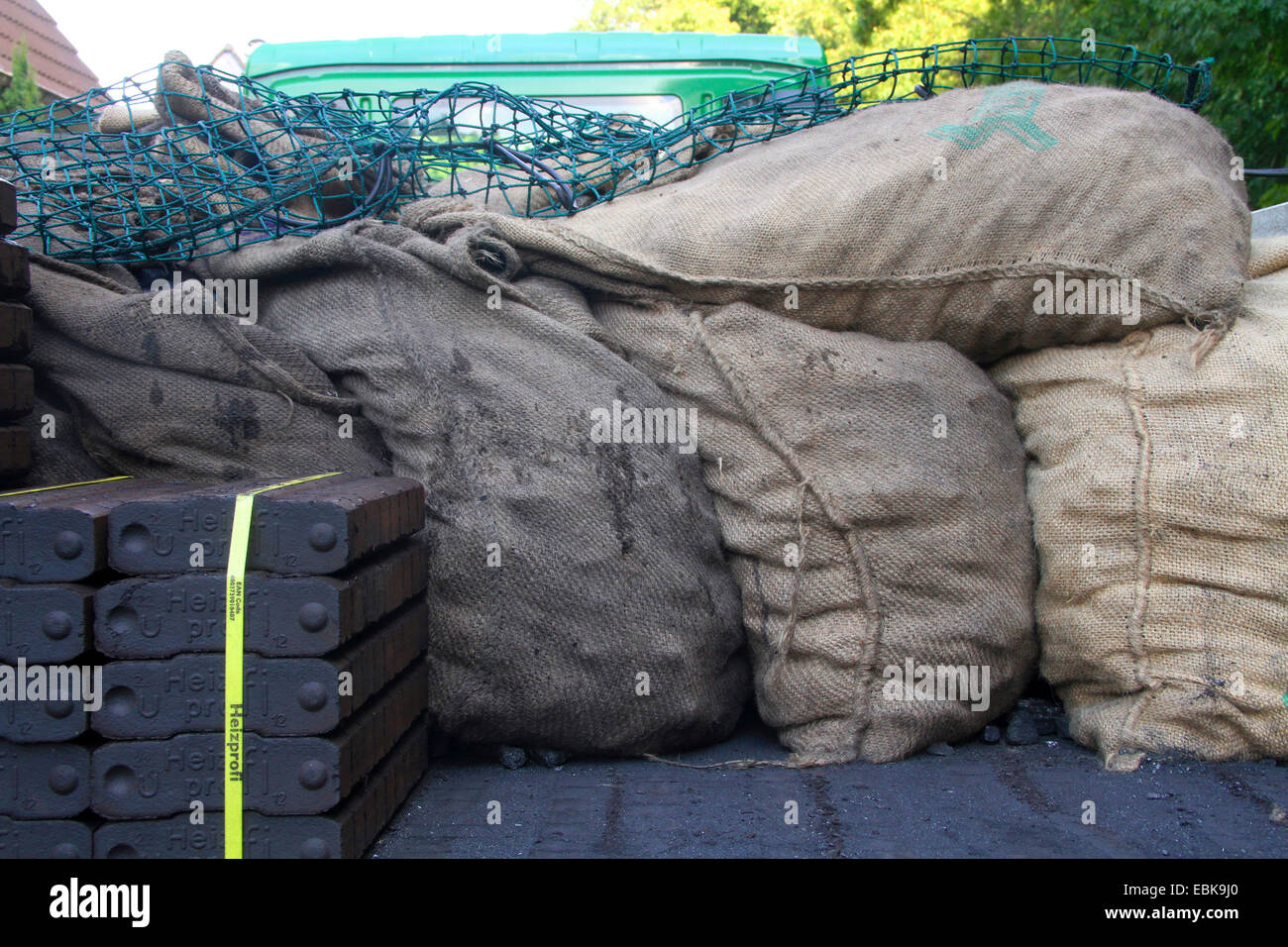 piled lignite briquettes and coking coal in sacks on a van, Germany - Stock Image