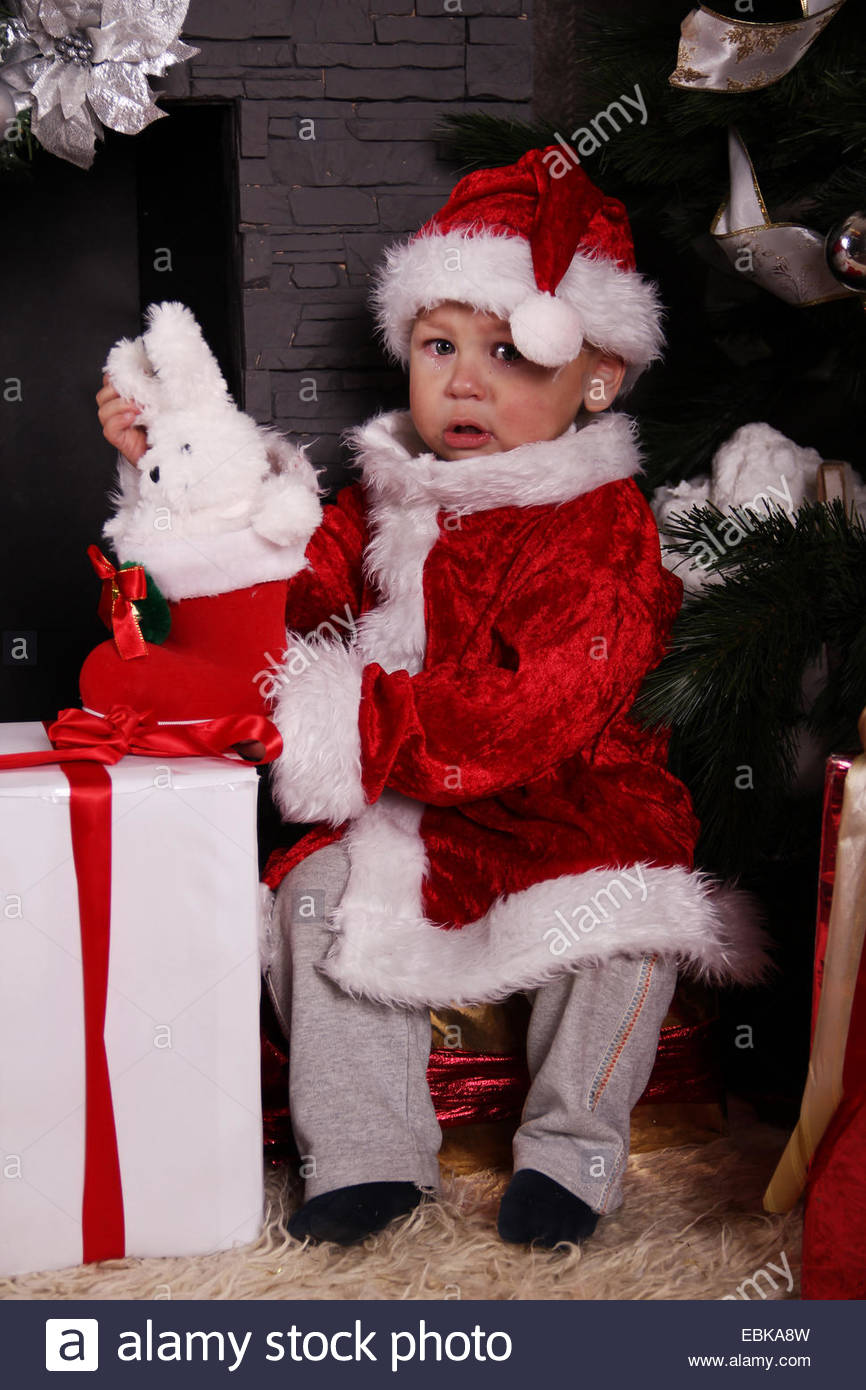 crying baby Santa Claus by the fireplace Stock Photo