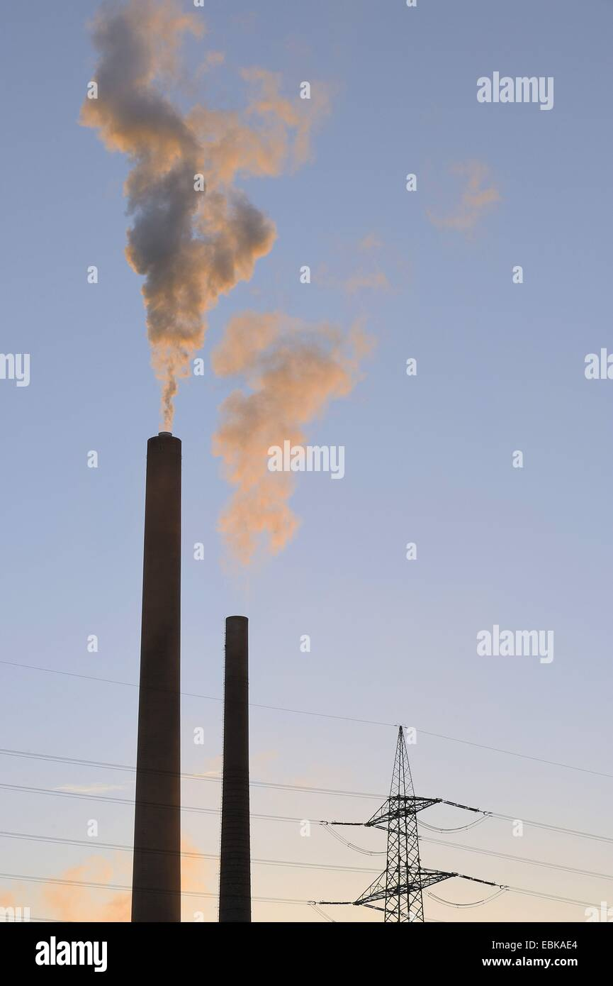 two chimney stacks smoking in the evening light in front of pylon, Germany, Bavaria, Stockstadt am Main Stock Photo