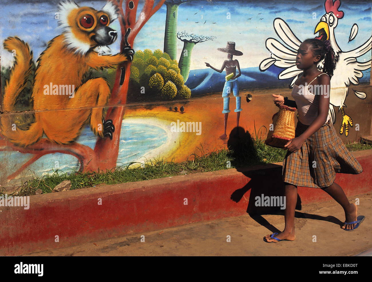young girl going in front of a painted wall, Madagascar, Nosy Be, Andoany, Hell Ville - Stock Image