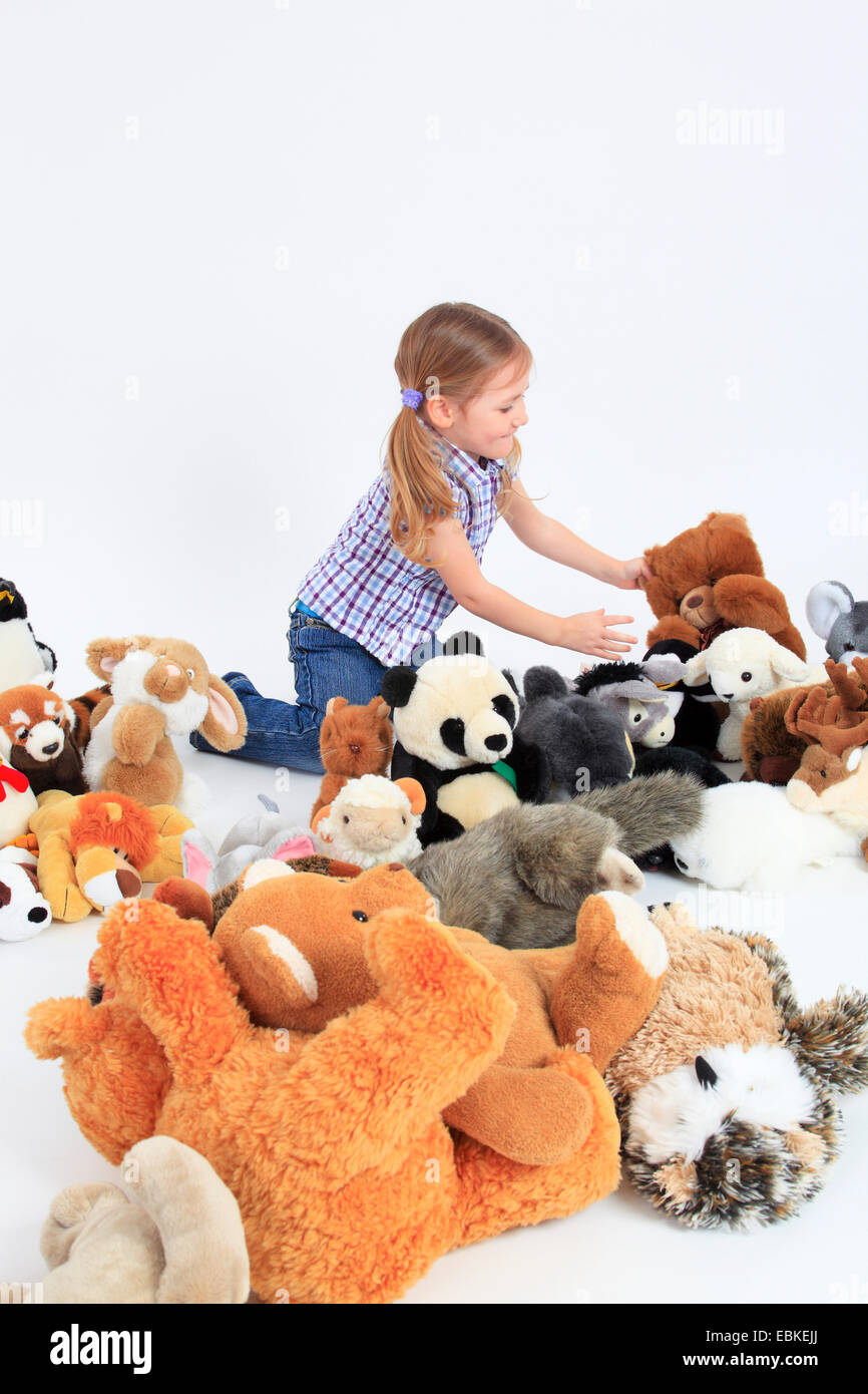 little happy girl playing with soft toys Stock Photo