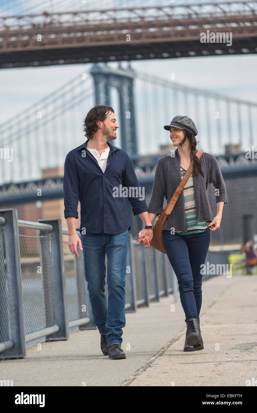 USA, New York State, New York City, Brooklyn, Couple walking on promenade, Brooklyn Bridge in background Stock Photo