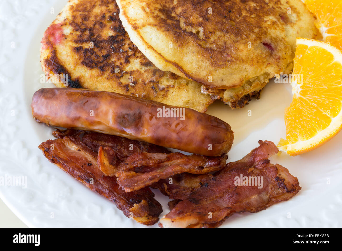 Breakfast sausage, bacon and pancakes with a slice of orange. - Stock Image