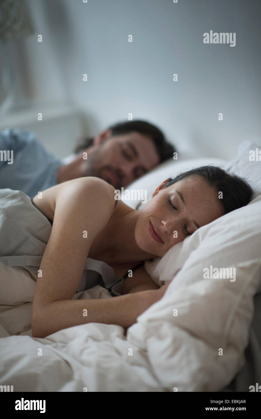 Couple sleeping together in bed at night - Stock Image
