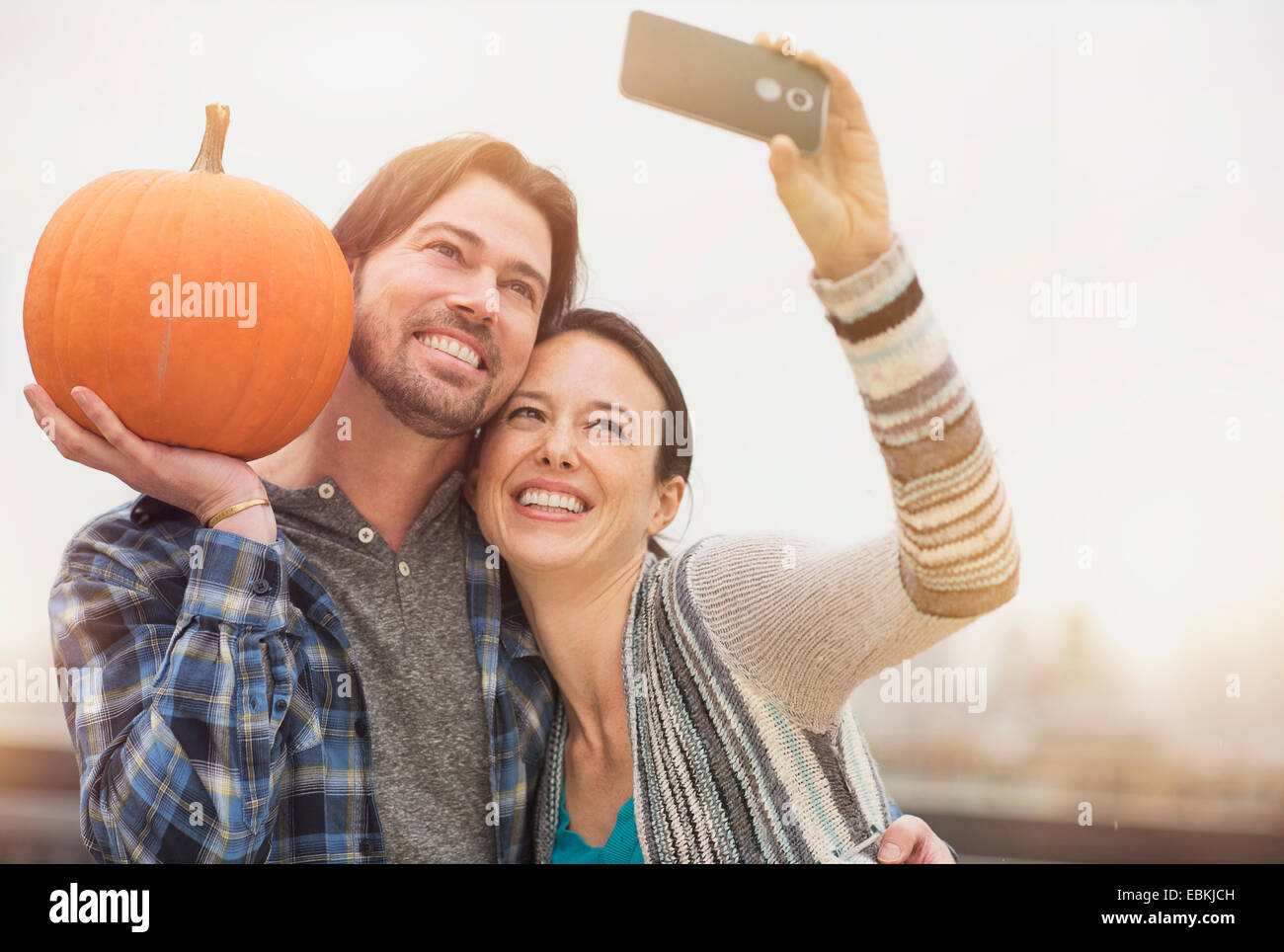 Couple taking selfie with mobile phone, man holding pumpkin Stock Photo