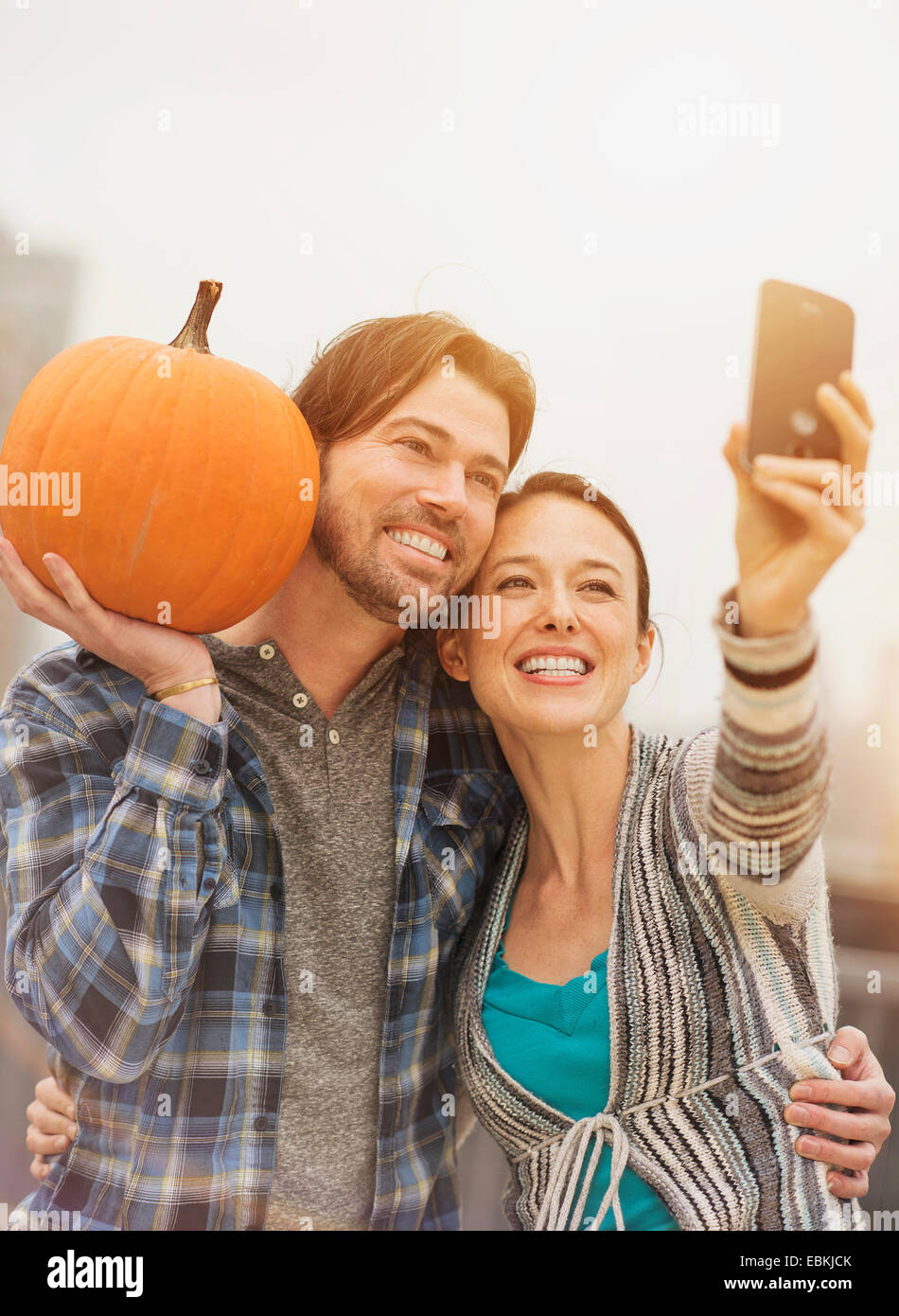 Couple taking selfie with mobile phone, man holding pumpkin - Stock Image