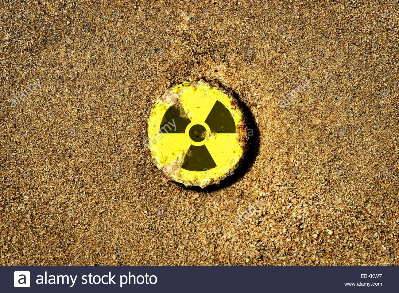 rusty bottle cap with the radioactivity symbol lying in the sand - Stock Image