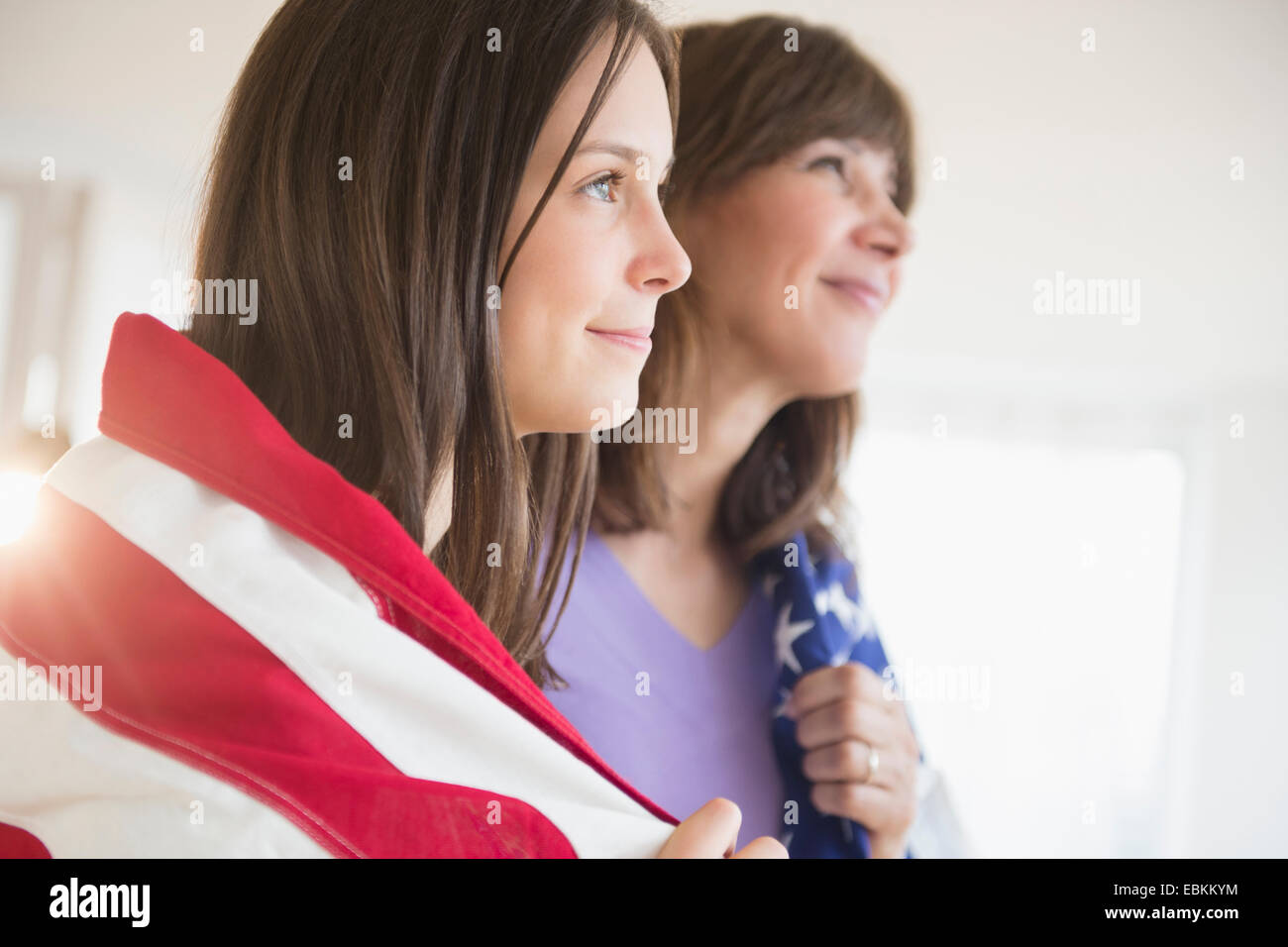 Teenage girl (14-15) and her mom wrapped in American Flag on Fourth of July Stock Photo